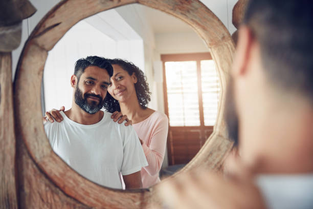 She gets him even when he doesn't get himself Shot of a mature man looking at his reflection in the mirror with his wife standing proudly behind him low self esteem stock pictures, royalty-free photos & images