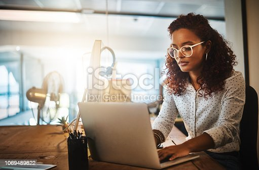 Shot of a young businesswoman using a laptop during a late night at work