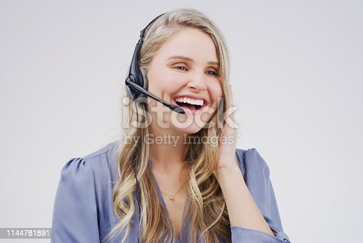 Studio shot of an attractive young female customer service representative wearing a headset against a grey background