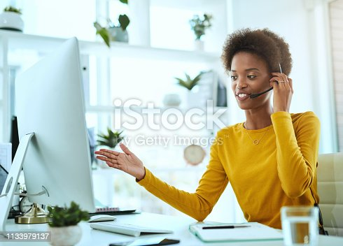 Shot of a young call centre agent working in an office