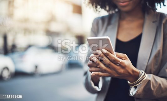 Closeup shot of a businesswoman using a cellphone in the city