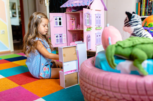 Adorable curious 5 year's old girl sitting on the floor and playing with stuffed animals, and dollhouse in her  playroom