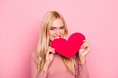 istock She is a heartbreaker! Close up portrait of jealous young attractive woman with long blonde hair. She is holding a heart and biting it, isolated on pink background 927803018