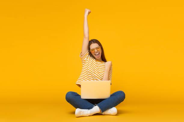 她是贏家!興奮的年輕女性與筆記本電腦查出在黃色背景 - 成功 個照片及圖片檔