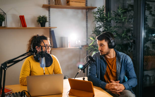 She is expert in radio interviews Photo of two young people recording a podcast in a studio recording studio stock pictures, royalty-free photos & images