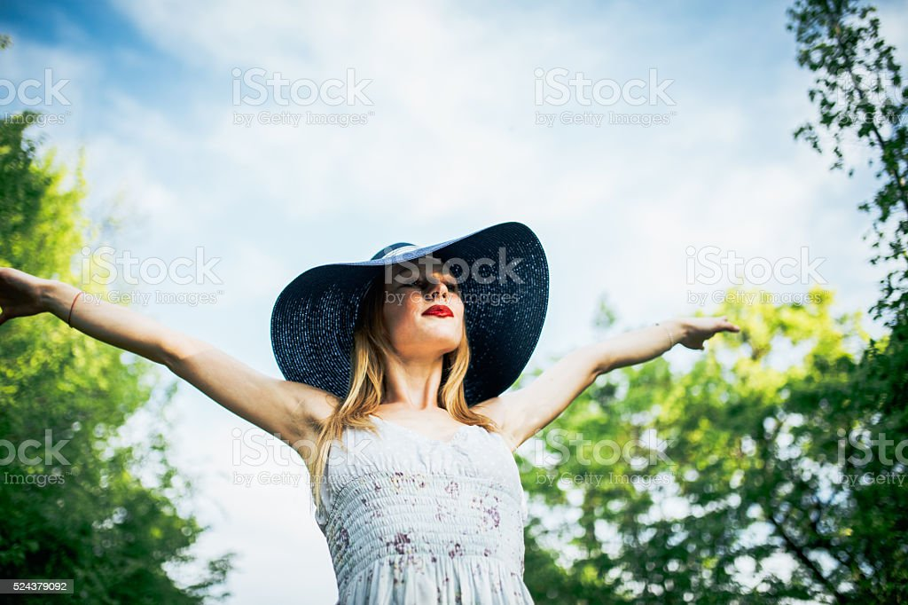 Young woman wearing a blue dress and a hat, enjoying the summer.