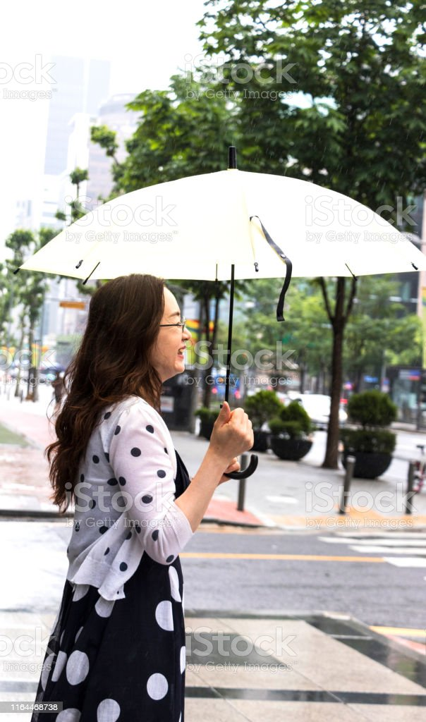 She is laughing happily on a rainy day, wearing an umbrella, meeting...