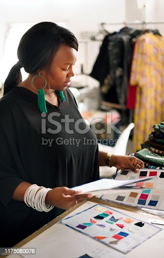 Shot of a woman dressmaker looking at color samples and choosing fabric at workshop