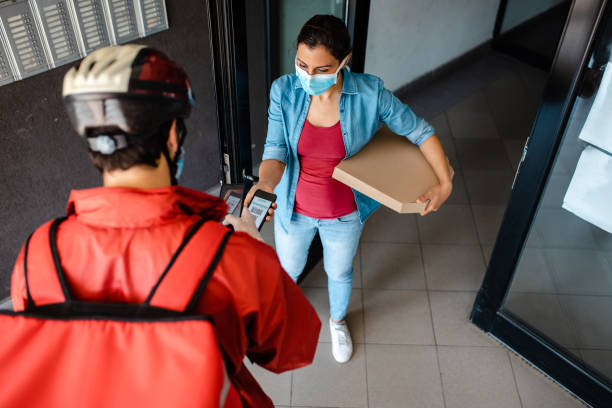 She is using a mobile app for a payment after she received a food delivery so she could avoid a contact during coronavirus pandemic stock photo