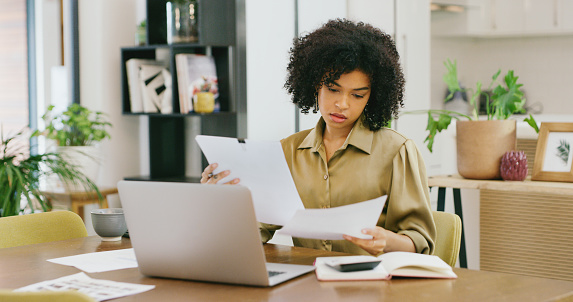 Shot of a young woman going through paperwork while working on a laptop at home