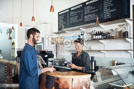 Shot of a barista serving a customer in a coffee shop