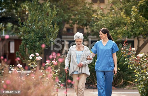 Shot of a caregiver and her patient out for a walk in the garden