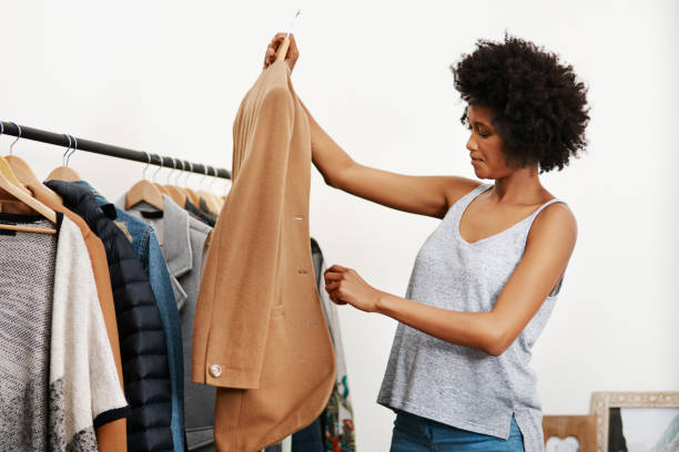 She knows what looks good on her Shot of a young woman getting dressed at home coat garment stock pictures, royalty-free photos & images