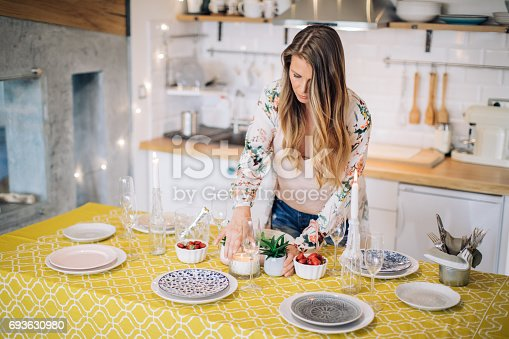 Woman arranging table for home dinner with friend or family.