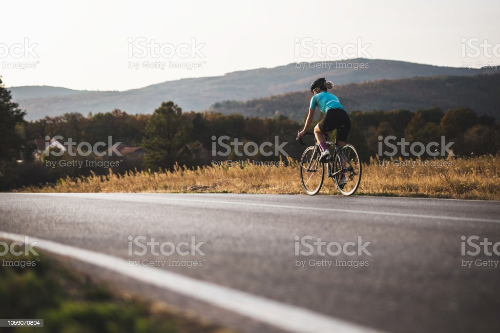 She likes to ride bicycle alone stock photo