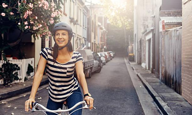 elle adore faire du vélo dans la ville - casque de protection au sport photos et images de collection