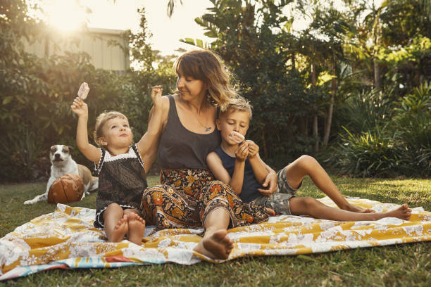 she loves her ice cream - mãe criança brincar relva efeito de refração de luz imagens e fotografias de stock