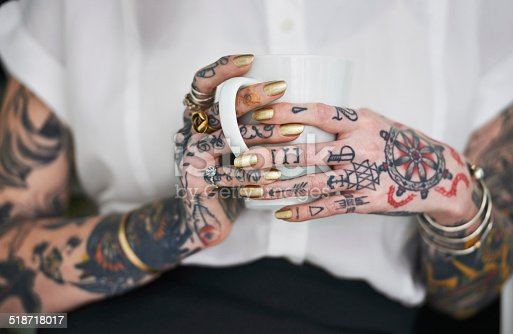 Shot of an unrecognizable tattooed businesswoman holding a mug