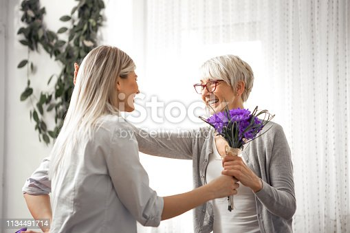 Beautiful young blonde was visiting her mother and brought her a bouquet of beautiful purple flowers.
