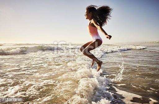 Shot of a young girl having fun at the beach
