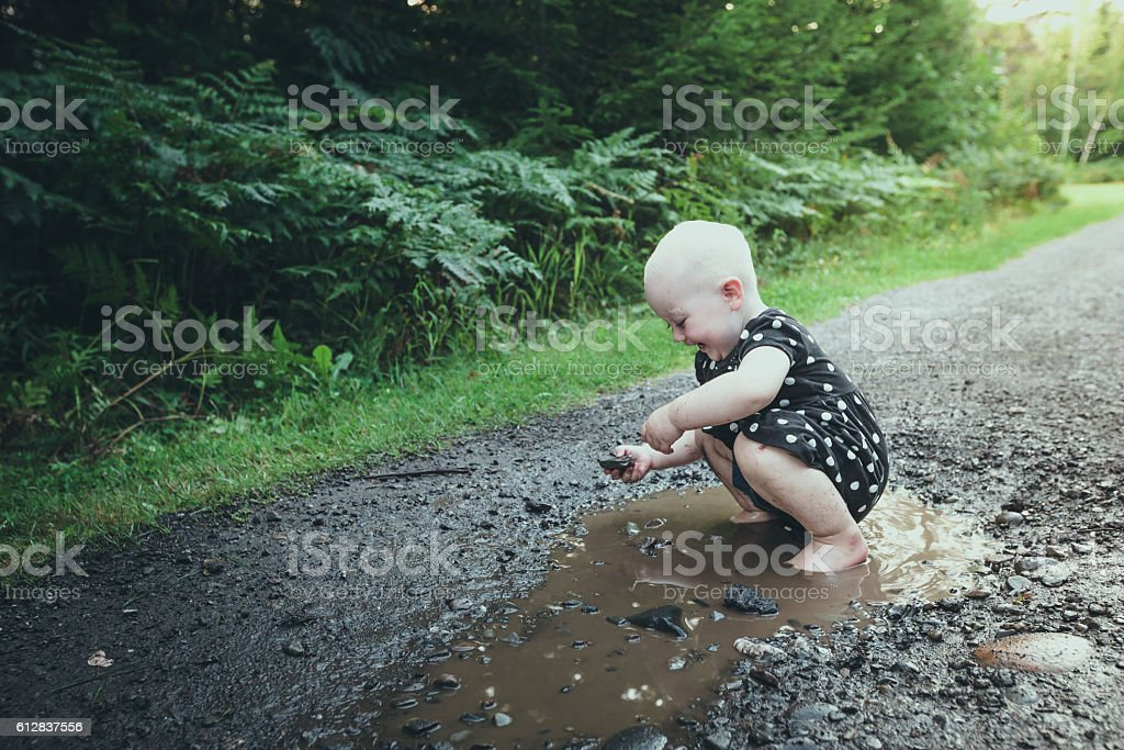 She loves playing in rainwater puddles. stock photo