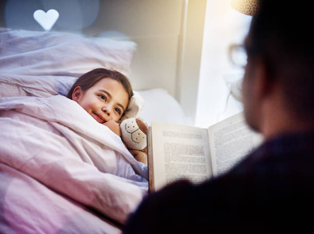She loves story time Cropped shot of a father reading his young daughter a bedtime story bedtime stock pictures, royalty-free photos & images