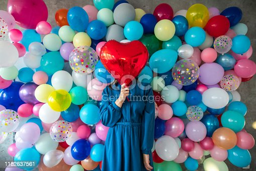 In front of wall with multi colored balloons standing woman in dress and holding heart shaped helium balloon, covering face