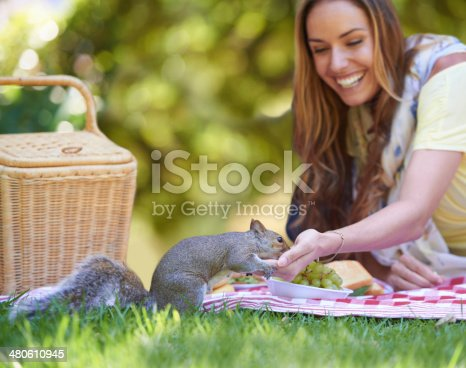 Shot of an attractive woman feeding a squirrel while enjoying a picnic