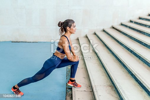Photo of Fitness woman doing lunges exercises for leg muscle workout training, outdoors. Active girl doing front forward one leg step lunge exercise. Young beautiful woman doing leg stretching before running upstairs.