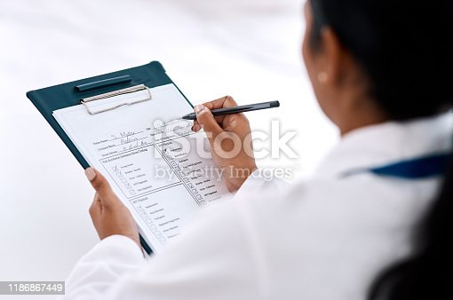 Cropped shot of an unrecognizable female doctor writing on a clipboard while working in her office