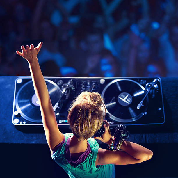 She makes the crowd go wild! Rear-view shot of a trendy young DJ mixing up some music with a crowd in the background dj stock pictures, royalty-free photos & images