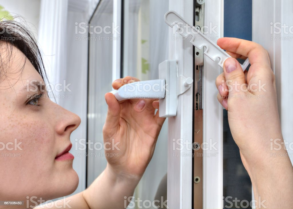 She mounts limiter for tilting and turning on PVC window. stock photo