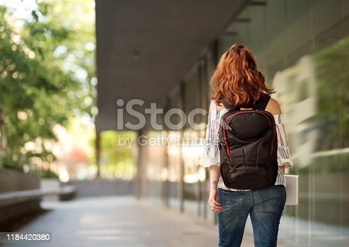 Rear view shot of a young female university student with backpack walking down a paved road