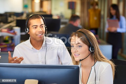 a young call centre representative greets a caller in a large open plan office as her supervisor watches over her shoulder and helps her through the call. Co-workers can be seen defocussed in the background .
