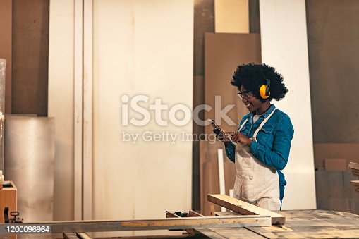 Photo of one Pretty young African-American female carpenter using a smartphone while working in her workshop.