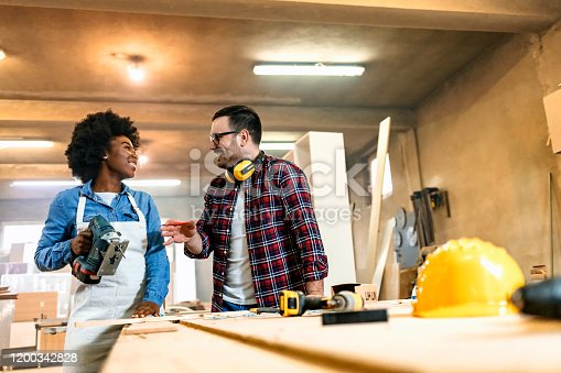 Male and African-American female Carpenters working on woodworking machines in carpentry shop. Happy woman works in a carpentry shop with her Confident handsome carpenter.