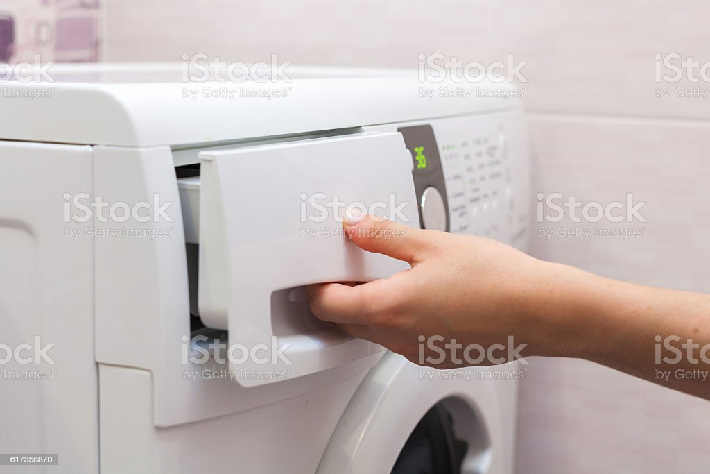 She pours the liquid powder in washing machine stock photo