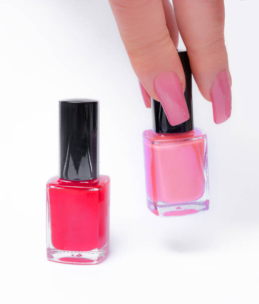 She prefers pink nail polish Mature woman's hand with pink nails lifts up a pink bottle identical to the color of her nails pink nail polish stock pictures, royalty-free photos & images