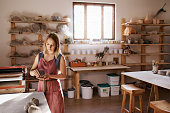 Cropped shot of a woman shaping a clay pot in her workshop