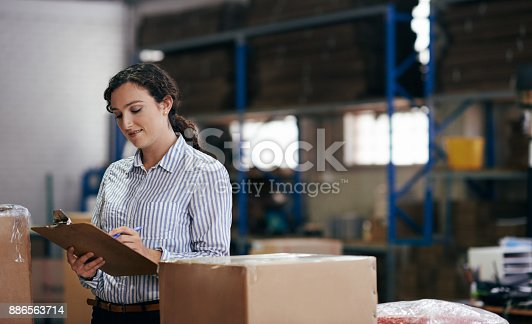 Cropped shot of an attractive young female warehouse worker using a clipboard to take stock