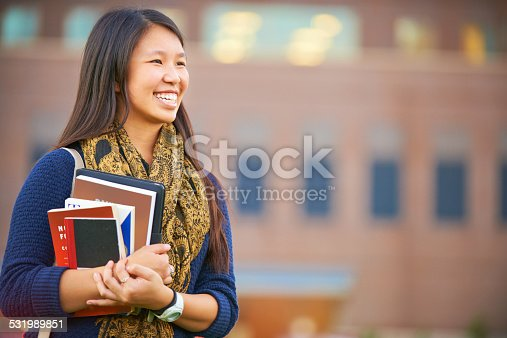 Shot of a young female student standing with her books on campus