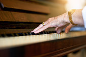 Shot of an unidentifiable senior woman playing the piano at home
