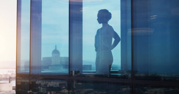 She succeeded faster than anyone else in the city Shot of a businesswoman looking thoughtful while looking out a window ceo stock pictures, royalty-free photos & images