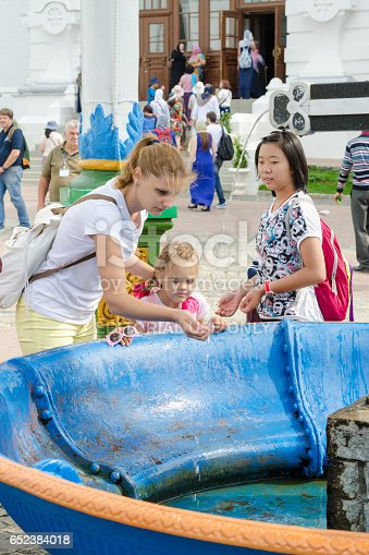Sergiev Posad - August 10, 2015: She visitor Holy Trinity St. Sergius Lavra washes the baby's face with holy water at the canopy over the cup with a cross
