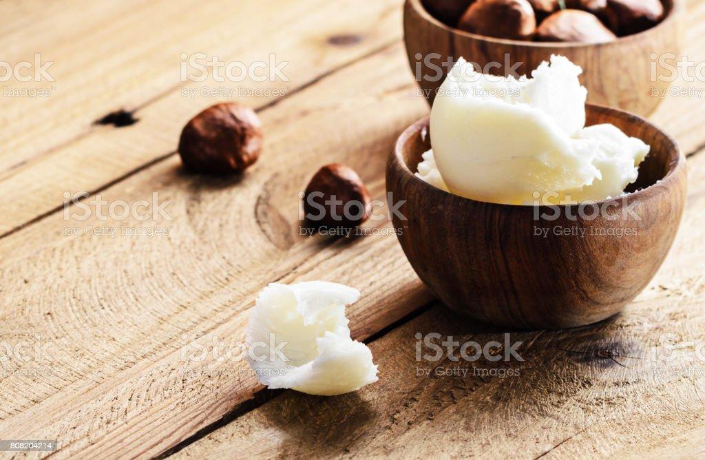Beurre de karité et noix sur une planche de bois, espace de la copie. - Photo