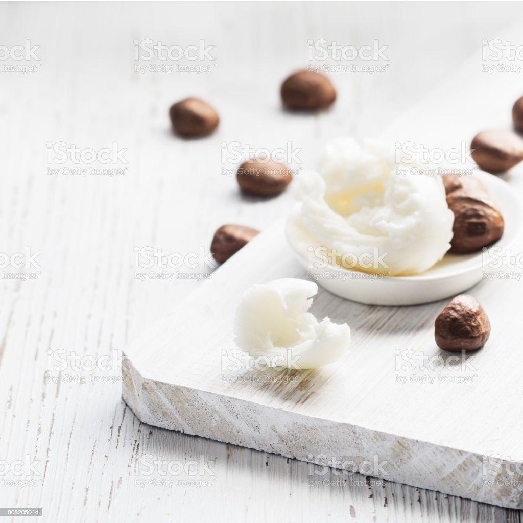 Beurre de karité et noix sur une planche de bois. - Photo