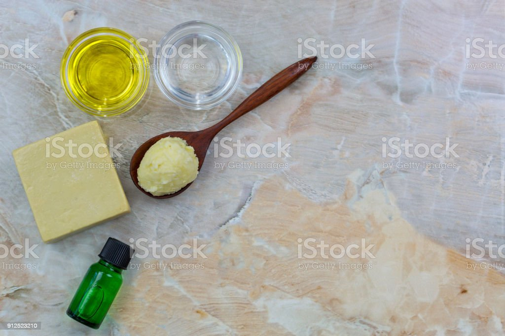 Shea butter, cold pressed Organic Jojoba Golden, Coconut oil, olive oil soap, essential oil extract on stone background stock photo