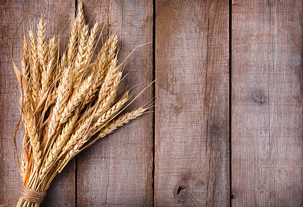 Sheaf of wheat ears on wooden table Sheaf of wheat ears on wooden table oat crop stock pictures, royalty-free photos & images