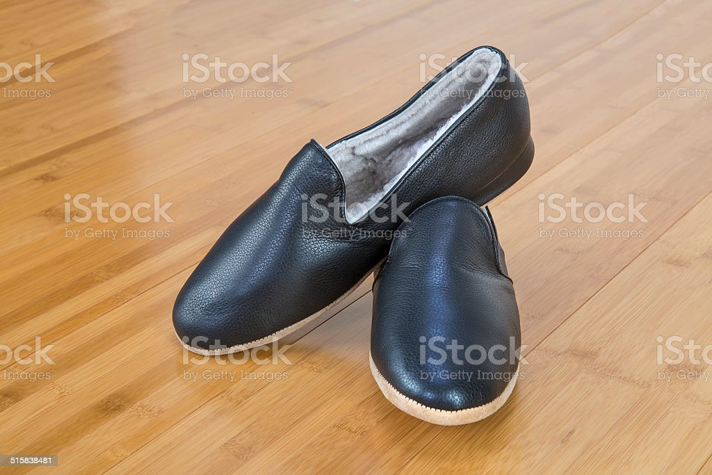 Shearling leather slippers on a wooden floor stock photo