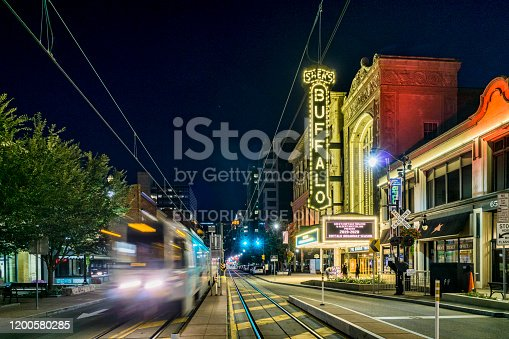 Buffalo, New York, USA - August 24, 2019: Lights from a passing streetcar pass in front of the Shea's Performing Arts Center in downtown Buffalo.